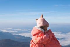 Zwei asiatische Kindermädchen, welche die Strickjacke und warmen Hut umarmen zusammen mit Liebe am schönen Nebel und am Berg trag lizenzfreie stockfotos