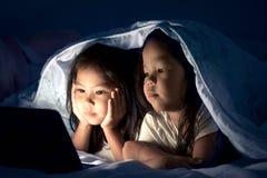 Zwei asiatische kleine Mädchen, die digitale Tablette unter Decke verwenden stockbild