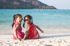 Zwei asiatische kleines Kindermädchen, die zusammen auf dem Strand nahe dem schönen Meer in den Sommerferien sitzen und spielen lizenzfreie stockbilder