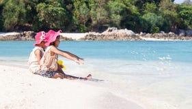 Zwei asiatische kleines Kinderm?dchen, die zusammen mit Sand auf dem Strand nahe dem sch?nen Meer in den Sommerferien sitzen und  lizenzfreie stockfotografie