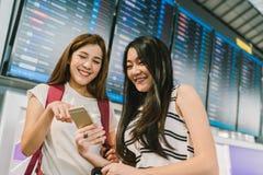 Zwei asiatische Mädchen, die zusammen Smartphone am Fluginformationsbrett im Flughafen verwenden On-line-Abfertigung, Zeitplananw lizenzfreie stockbilder