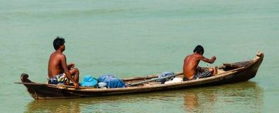 Zwei asiatische Männer, die hölzernes Boot auf einem Fluss rudern stockfoto