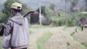 Zwei asiatische weibliche Landarbeiter, die grabende Werkzeuge halten, betrachten Kamera und überschreiten vorbei stock footage