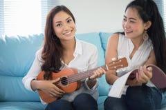 Zwei Asien-Frauen haben den Spaß, der Ukulele spielt und am hom lächelt stockfotografie