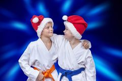 Zwei Athleten in den Kappen von Santa Claus auf einem Hintergrund des blauen Strahlens stockfotografie