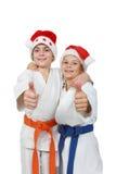 Zwei Athleten in der Kappe Santa Claus zeigen den Super Finger stockfotografie