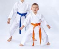 Zwei Athleten in karategi Stand im Gestellkarate auf einem weißen Hintergrund lizenzfreie stockfotos