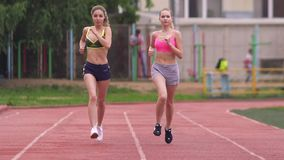 Zwei Athleten konkurrieren im Rennen am Stadion morgens, im Sommer, auf der Straße stock video