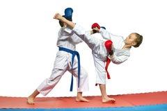 Zwei Athleten mit Überlagerungen auf den Händen bilden zusammengepaßte Übungen von Karate aus lizenzfreie stockbilder