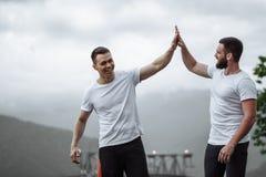 Zwei Athleten stehen nach intensivem Trainingstraining im Freien in der Berglandschaft still stockfotografie