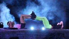 Zwei athletisch, die sexy jungen Frauen, Eignung tuend trainiert in den Paaren, nachts, im hellen Rauche, Nebel, im Licht mehrfar stock video footage