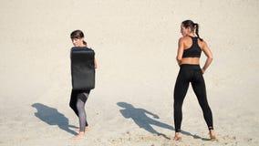 Zwei athletisch, junge Frauen in den schwarzen Eignungsanzügen nehmen an einem Paar, ausarbeiten Tritte, auf einem einsamen Stran stock footage