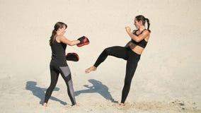 Zwei athletisch, junge Frauen in den schwarzen Eignungsanzügen nehmen an einem Paar, ausarbeiten Tritte, auf einem einsamen Stran stock video