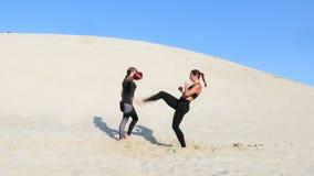 Zwei athletisch, junge Frauen in den schwarzen Eignungsanzügen nehmen an einem Paar teil, arbeiten Tritte aus, bilden aus, führen stock footage