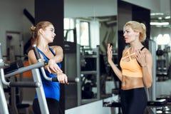 Zwei athletische blonde Frauen, die in der Turnhalle sprechen Mädchen verständigt sich mit Trainer Lizenzfreies Stockfoto