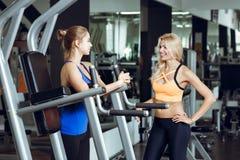 Zwei athletische blonde Frauen, die in der Turnhalle sprechen Mädchen verständigt sich mit Trainer Stockfotografie