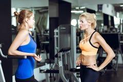 Zwei athletische blonde Frauen, die in der Turnhalle sprechen Mädchen verständigt sich mit Trainer Stockfoto