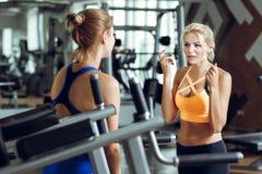 Zwei athletische blonde Frauen, die in der Turnhalle sprechen Mädchen verständigt sich mit Trainer Lizenzfreie Stockbilder