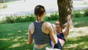 Zwei athletische Mädchen spielen Sport auf dem Gras, einer von ihnen tut eine Übung auf der Presse stock footage