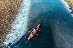 Zwei athletische Mannfl??e auf einem roten Boot im Fluss stockfotos