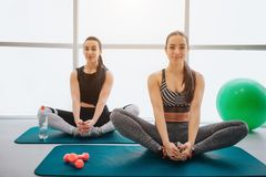 Zwei attraktiv und gut gebaut junge Frauen sitzen auf Matten- und Ausdehnungsbeinen Sie schauen auf Kamera und Lächeln Modelle ha stockfotos