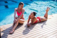 Zwei attraktive blonde und Brunettemädchen mit dem langen Haar liegen auf Flor nahe Pool Sie tragen Bikini und Badeanzug sie Lizenzfreie Stockfotos