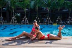 Zwei attraktive blonde und Brunettemädchen mit dem langen Haar liegen auf Flor nahe Pool Sie tragen Bikini und Badeanzug sie Lizenzfreie Stockfotografie