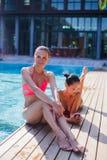Zwei attraktive blonde und Brunettemädchen mit dem langen Haar liegen auf Flor nahe Pool Sie tragen Bikini und Badeanzug sie Stockfoto