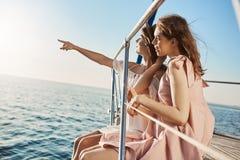 Zwei attraktive europäische Frauen, die am Bogen der Yacht, etwas beim Zeigen betrachtend auf Küste sitzen Freundgenießen lizenzfreies stockbild