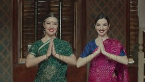 Zwei attraktive Frauen im Sari mit strahlendem Lächeln