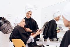 Zwei attraktive Frauen mit Tüchern auf Haar wählen Frisurart auf Tablette im Friseur lizenzfreie stockfotografie