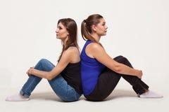 Zwei attraktive Frauen sitzen zurück zu Rückseite lizenzfreie stockfotografie