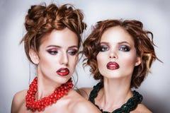 Zwei attraktive Freundinnen - blond und Brunette auf weißem Hintergrund Stockfotografie