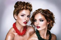 Zwei attraktive Freundinnen - blond und Brunette auf weißem Hintergrund Stockbilder