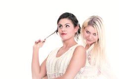 Zwei attraktive Freundinnen - blond und Brunettelächeln Stockfotografie