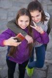 Zwei attraktive Freundinnen, die draußen Selbstporträt mit ihrer Telefon-Kamera nehmen Stockfotos