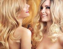 Zwei attraktive Freundinnen, die um ihrem Haar sich kümmern stockfoto