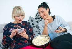 Zwei attraktive Freundinnen mit Handy und Popcorn Lizenzfreie Stockfotografie
