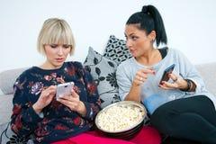 Zwei attraktive Freundinnen mit Handy und Popcorn Lizenzfreie Stockbilder