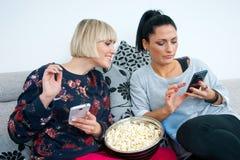 Zwei attraktive Freundinnen mit Handy und Popcorn Stockbild