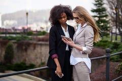 Zwei attraktive Geschäftsfrauen, die den Schirm auf einer Tablette betrachten Eine Frau ist Schwarzes und andere ist blond Lizenzfreies Stockfoto