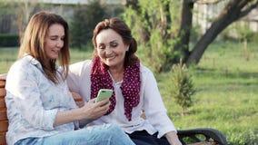 Zwei attraktive glückliche alte und Frauenfreundinnen von mittlerem Alter, die einen Smartphone verwenden stock video