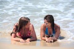 Zwei attraktive junge Frauen, die auf einem sonnigen Strand nahe dem Wasser liegen Lizenzfreie Stockfotografie