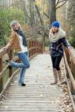 Zwei attraktive junge Frauen, die auf einer Holzbrücke lachen Stockbilder