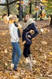 Zwei attraktive junge Frauen, die mit fallenden Blättern aufwerfen Stockbilder