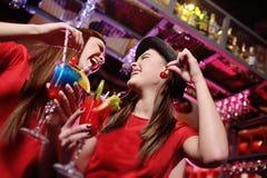 Zwei attraktive junge Freunde an einer Partei lachen mit Cocktails in den Händen einer Bar Stockfotografie