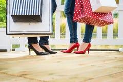 Zwei attraktive junge Freundinnen, die einen Bruch nach succesfull Einkaufen genießen Stockbild