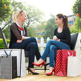 Zwei attraktive junge Freundinnen, die einen freien Tag nach dem erfolgreichen Einkaufen genießen Stockfotografie
