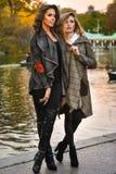 Zwei attraktive kaukasische Frauen, die gegen den See im Park aufwerfen Stockfotografie