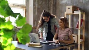 Zwei attraktive Kollegen besprechen aufpassende Anmerkungen des Designs im Notizbuch, im Laptopschirm und in den Fotos auf Tabell stock footage